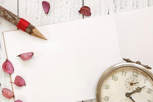 Fotografia stock matita d'annata della sveglia dei petali viola del fiore della tavola di legno verniciata bianca d'annata di disposizione piana