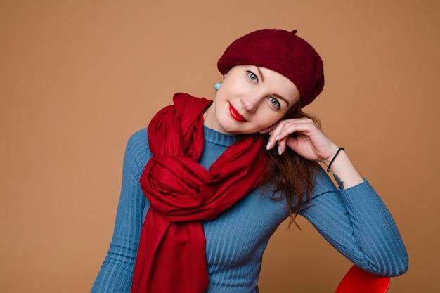 Ritratto in studio di un'affascinante signora che indossa un berretto rosso e una sciarpa su un abito blu leggermente sorridente...