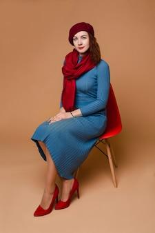 Ritratto in studio di una donna affascinante che indossa un berretto rosso e una sciarpa su un vestito blu