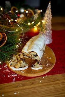 Pane natalizio tedesco stollen, stollen natalizio su fondo di legno, dessert di pasticceria festivo tradizionale.
