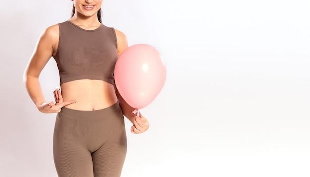 Concetto di mal di stomaco - stomaco gonfio, crampi, sollievo dal dolore. giovane donna che tiene un palloncino rosa accanto alla sua vita.
