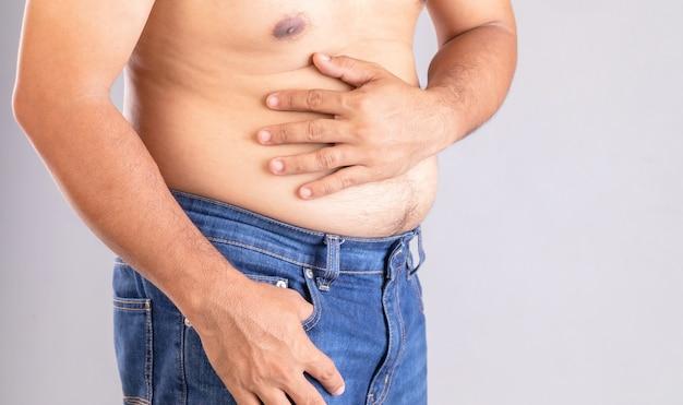 Mal di stomaco o dolore sul concetto di pancia: uomo grasso usando la mano e premendo sullo stomaco