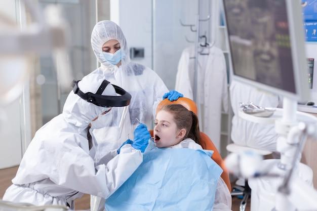 Stomatologo nel corso del trattamento della carie per bambino vestito con tuta dpi come precauzione di sicurezza dentista in tuta coronavirus che utilizza uno specchio curvo durante l'esame dei denti del bambino.