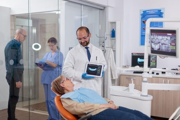 Stomatologo che tiene i raggi x di una donna anziana seduta su una sedia arancione nell'auto medica dei denti dell'armadietto del dentista...
