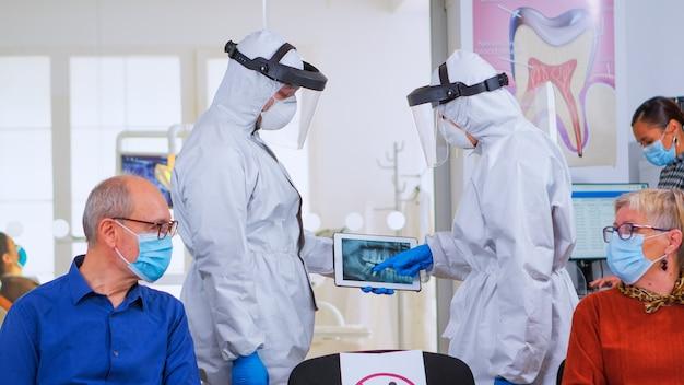 Medici stomatologici con lo studio complessivo della radiografia digitale nell'area di attesa, pianificando un intervento chirurgico durante la pandemia di coronavirus mentre i pazienti anziani discutono seduti su sedie mantenendo le distanze.
