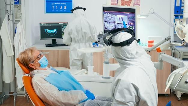 Stomatologo in tuta e paziente che guarda la radiografia dentale digitale che la rivede prima dell'intervento chirurgico durante la pandemia di covid-19. equipe medica che indossa visiera, maschera di protezione e guanti in clinica