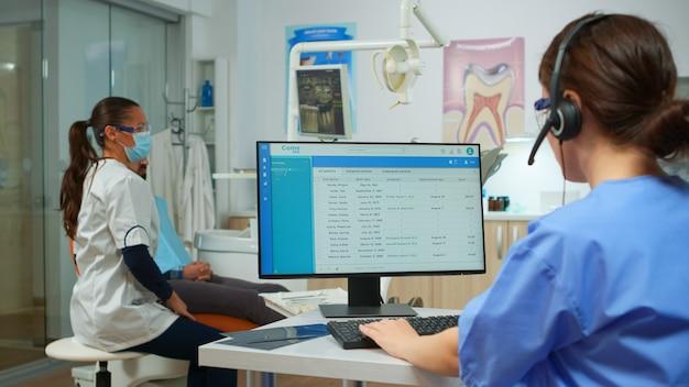 Infermiera stomatologa che parla con i pazienti utilizzando l'auricolare che fa appuntamenti dal dentista seduto di fronte al computer mentre il medico sta lavorando con lo sfondo del paziente esaminando il problema dei denti