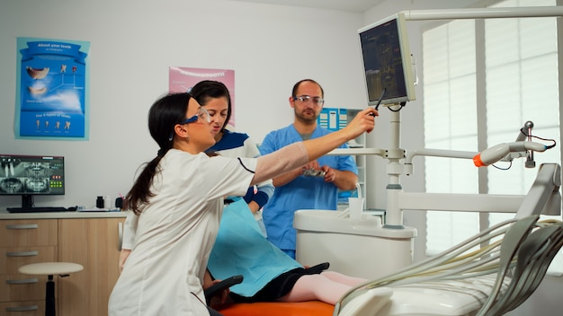 Stomatologo che indica sullo schermo digitale che spiega i raggi x a madre e bambino. medico e infermiere che lavorano insieme nella moderna clinica stomatologica, esaminando, mostrando la radiografia dei denti sul monitor