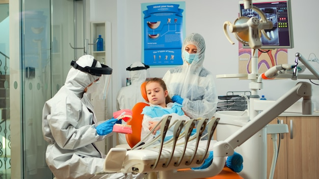 Stomatologo in tuta dpi che tiene in mano un modello in gesso della mandibola che parla con una paziente. equipe medica che indossa tuta protettiva, maschera, guanti, che mostra una corretta igiene dentale utilizzando lo scheletro dei denti