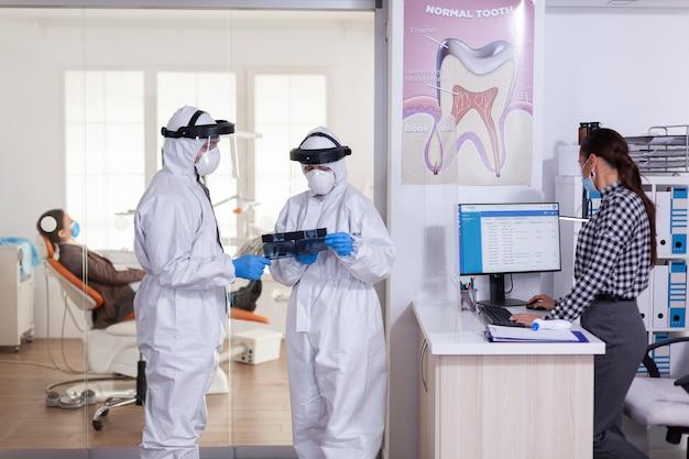 Assistente di stomatologia che indossa la tuta in dpi con scudo facciale come precauzione di sicurezza con il dentista che discute i raggi x nell'area di attesa della clinica odontoiatrica