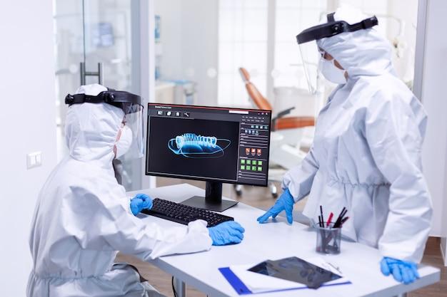 Il team di stomatologia che guarda la mascella del paziente sullo schermo del monitor vestito con una tuta in dpi. specialista medico che indossa indumenti protettivi contro il coronavirus durante l'epidemia globale che esamina la radiografia in odontoiatria
