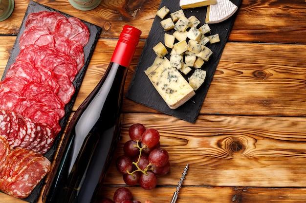 Tavole di pietra con affettatura di formaggio e salsiccia sulla tavola di legno si chiudono