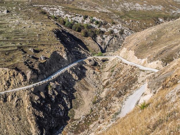 Ponte di pietra e serpentina di montagna in montagna. vista aerea
