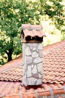 Camino in pietra su un tetto di tegole su uno sfondo di verde