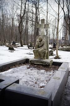 Croce di pietra sulla tomba con statua di donna che piange. nel cimitero innevato tra alberi spogli - cimitero luterano di smolenskoe, russia, san pietroburgo, marzo 2021
