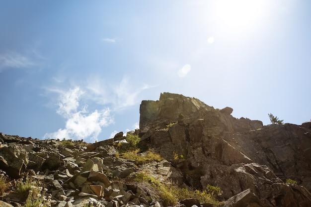 Depositi di pietra sulla cima di un'alta montagna sullo sfondo del cielo azzurro con un sole splendente in una giornata estiva