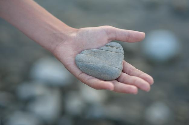 Pietra a forma di cuore su una mano su uno sfondo neutro