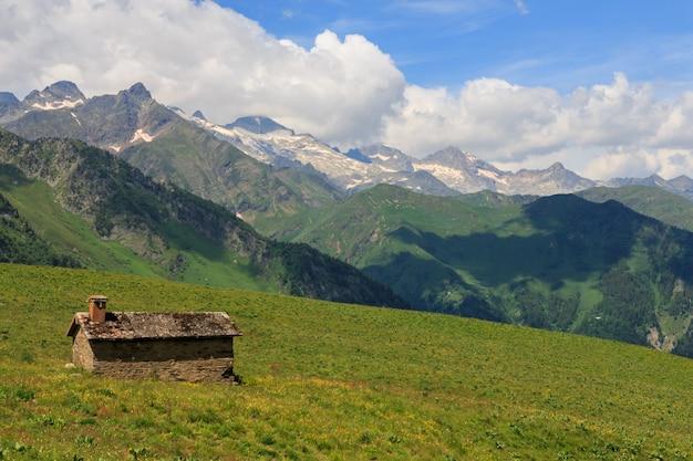 Capanna di pietra in campo verde con montagne e nuvole sullo sfondo