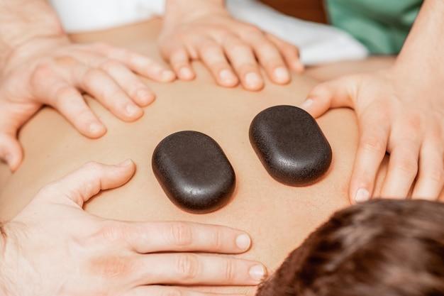Massaggio con pietre sulla schiena dell'uomo.