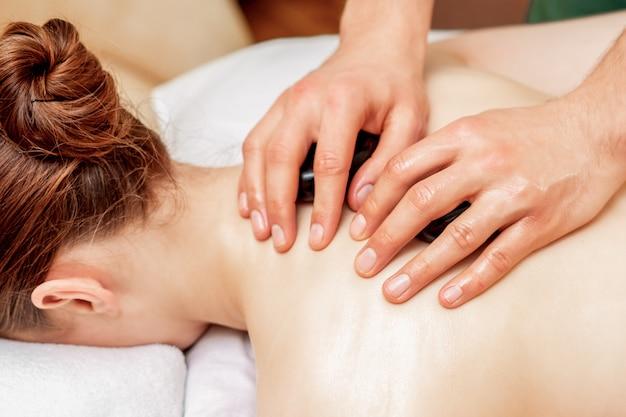 Massaggio con pietre sul retro della donna