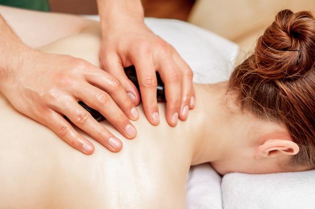 Massaggio con pietre sul retro della donna.
