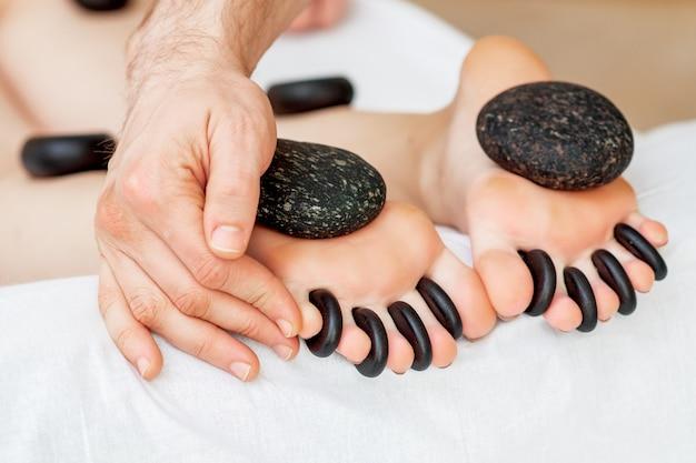 Massaggio con pietre sulle dita dei piedi.