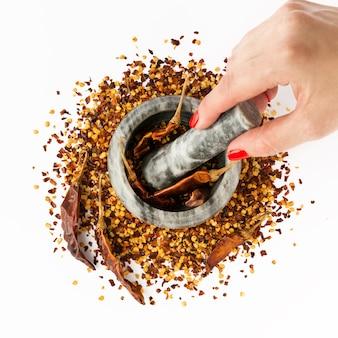 Ciotola di pietra del mortaio piena di pepe di caienna rosso tritato. la mano della donna tiene un pestello. fiocchi e semi secchi del peperoncino rosso isolati su un bianco. spezie fatte in casa ingredienti per cucinare.