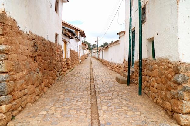 Percorso di pietra tra i vecchi edifici in pietra del villaggio andino di chinchero nella valle sacra degli incas peru