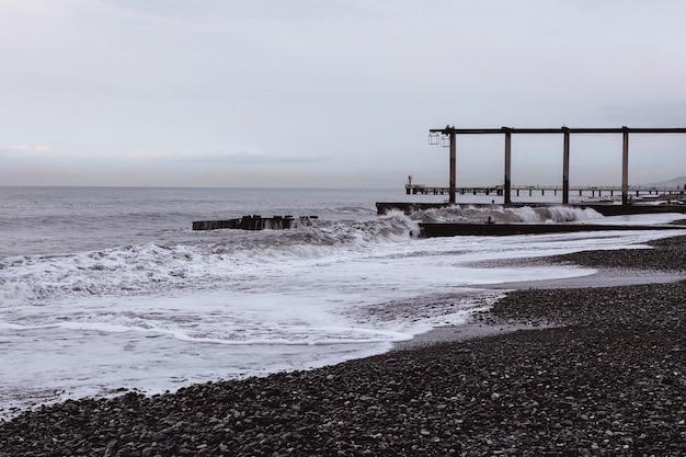 Molo di pietra sulla costa con onde e linea dell'orizzonte