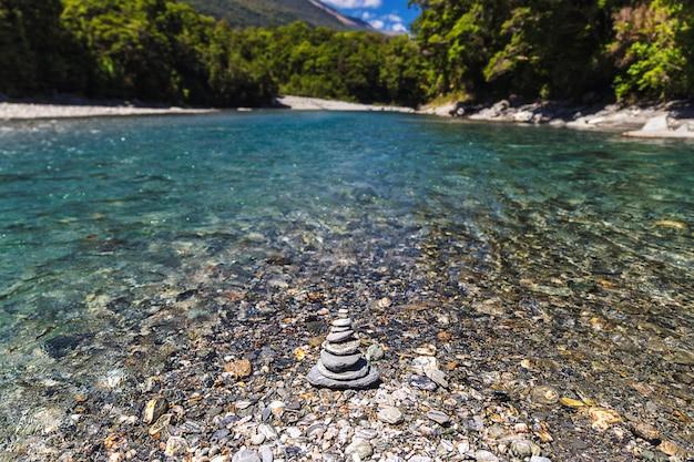 Piramide di pietra sulla riva del fiume con acqua turchese chiaro, nuova zelanda