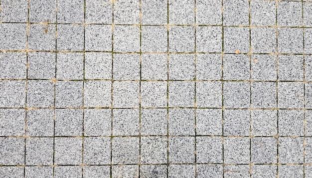 Marciapiede in pietra. pietre per lastricati su strade e marciapiedi nella parte vecchia della città. fondo del materiale di pietra per lastricati. granito, ciottoli. modello di pavimento in cemento per lo sfondo.