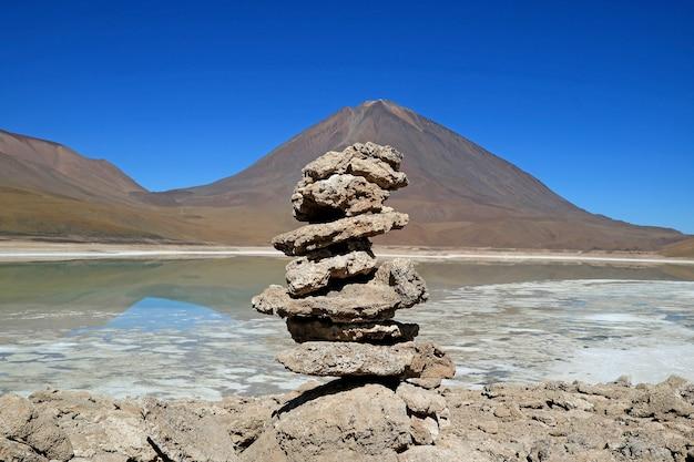 Stack di pietra realizzato da viaggiatori sulle rive del lago verde laguna verde, bolivia