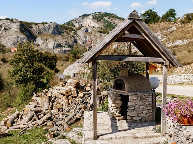Una stufa in pietra in un gazebo in montagna un terrapieno di legna da ardere