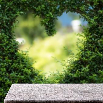 Tavolo in pietra sullo sfondo del display quadrato della luce solare della pianta dell'amore all'aperto