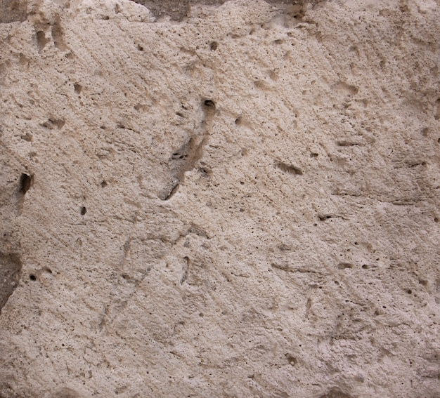 Struttura di pietra in beige con fori. sfondo.