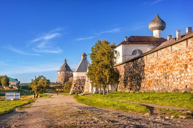 Torri di pietra del monastero di solovetsky e la strada lungo le rive della baia della prosperità sulle isole solovetsky sotto i raggi del sole al tramonto
