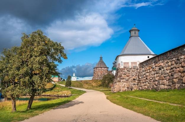 Torri di pietra del monastero di solovetsky sulle isole solovetsky, un albero e una strada sotto i raggi del sole autunnale