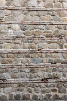 Muro di pietra e sfondo di cemento