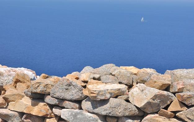 Muro di pietra che si affaccia su un mare blu