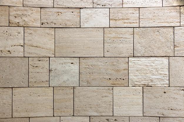 Trama di muro di pietra, piastrelle quadrate di travertino giallo. elemento di design o sfondo.