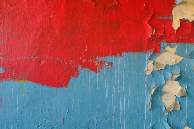 Muro di pietra con vecchia vernice blu e rossa. sfondo grunge. foto di alta qualità