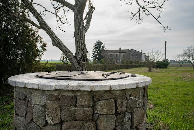 Dettaglio pozzo in pietra immerso in un giardino d'inverno
