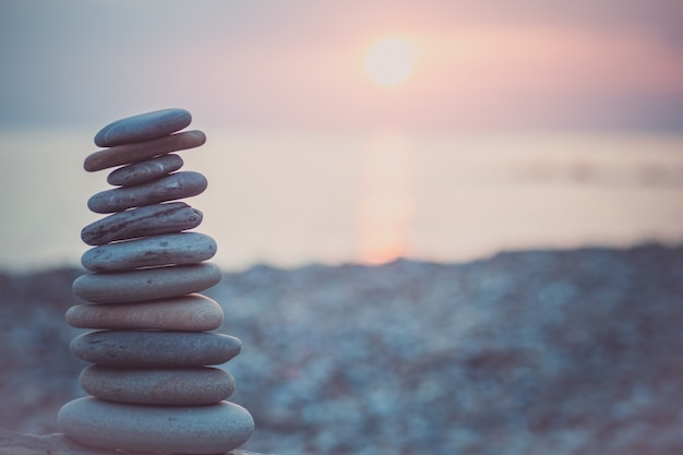 Piramide di pietre sulla sabbia che simboleggia zen, armonia, equilibrio. oceano al tramonto sullo sfondo.