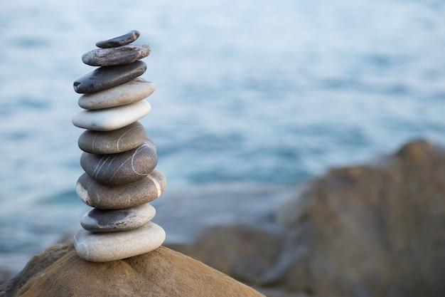 Piramide di pietre sulla sabbia che simboleggia zen, armonia, equilibrio.
