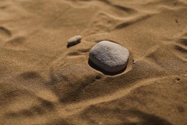 Pietre sulla parete della spiaggia di sabbia. carta da parati naturale, trama. messa a fuoco selettiva. far fronte allo spazio