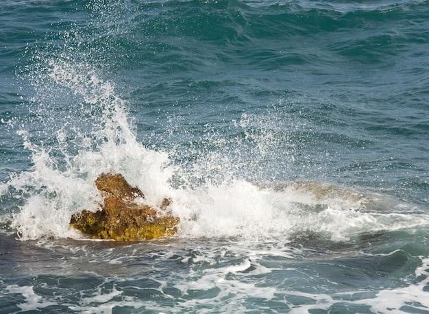 Costa del mare pietroso e onda con spruzzi