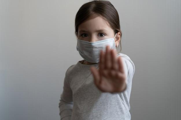 Fermare il concetto di epidemia di coronavirus o covid 19 - la ragazza con la maschera protettiva medica mostra un gesto di arresto con la mano - la ragazza ha teso il palmo con paura, concetto di quarantena o isolamento domestico