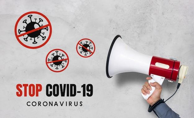 Ferma il concetto covid-19. mano dell'uomo che tiene megafono sul muro di mattoni bianco