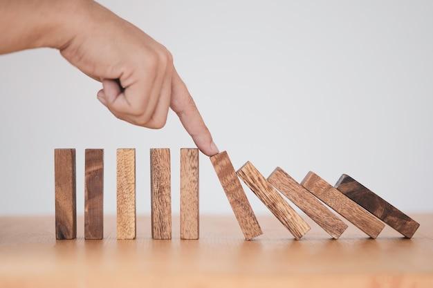 Fermare la crisi e il concetto di gestione del rischio, uomo che usa il dito per fermare il domino in legno che cade su un blocco di legno ancora in piedi.