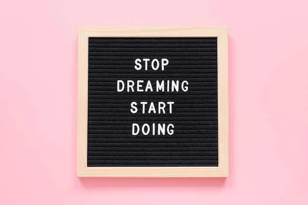 Smetti di sognare inizia a fare. citazione motivazionale sulla lavagna su sfondo rosa. citazione ispiratrice di concetto